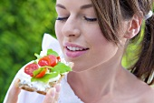 Young woman eating crispbread with cottage cheese, tomato & basil