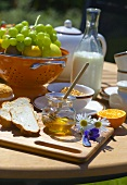 Breakfast out of doors (honey, bread, cereal, fruit)