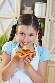 Girl eating a slice of pizza