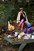 Young woman sitting by campfire with laid table (autumn)