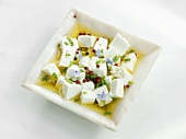 Feta cheese with olive oil, herbs and pink peppercorns