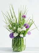 Chives with purple and white flowers in a glass
