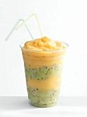 A beaker of mango and kiwi fruit smoothie