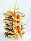 A stack of crispbread and carrots with tape measure