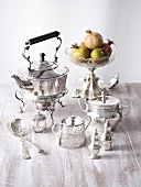 Silver tea set and bowl of pomegranates