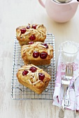 Friands with cherries and almonds on cake rack