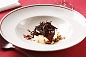 Ice cream with chocolate sauce and pine nuts