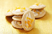 Almond macaroons with icing and orange peel