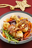 Bacon-wrapped chicken drumsticks on vegetables