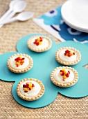 Vanilla cream tarts with small pieces of fruit