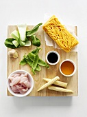 Ingredients for Hokkien noodles with chicken on chopping board (overhead)