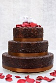 Chocolate wedding cake with rose petals and pair of doves
