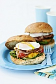 Poached egg and bacon in bread rolls for breakfast