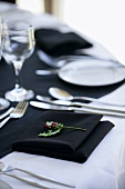 Laid table with white tablecloth and black napkins