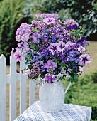 Jug of purple flowers out of doors