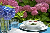 Vegetable cream soup and hydrangeas on table out of doors