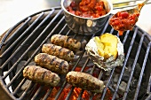 Cevapcici with baked potato and tomatoes on barbecue