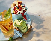 Apple iced tea, cucumber slices on crispbread & berry muesli