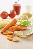 Peeled carrots and potato, tomatoes and tomato juice
