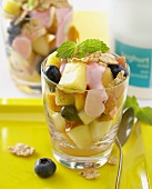 Fruit salad with berry yoghurt and cereal flakes in glass