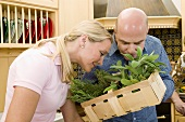 Couple examining fresh herbs in kitchen
