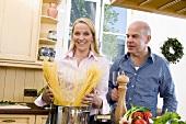 Frau gibt Spaghetti in Kochtopf, daneben Mann mit Rotweinglas
