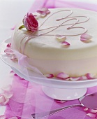White cake with rose petals, pink hearts and bow