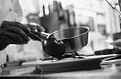 Koch richtet Gericht auf einem Teller an (s-w-Aufnahme)