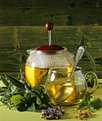 Herb tea in teapot and glass cup