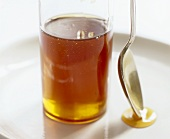 Glass of honey and spoon