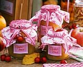 Gläser mit Apfelmus, dekoriert mit Stoff und Zieräpfeln