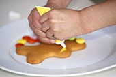 Child's hands decorating a gingerbread man with writing icing