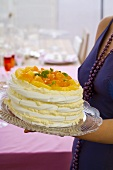 Young woman holding layered meringue cake with citrus fruit
