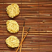 Chinese egg noodles and chopsticks on bamboo mat