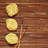 Chinesische Eiernudeln und Essstäbchen auf Bambusmatte