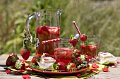 Strawberry punch, fresh strawberries, petit fours on garden table