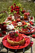 Strawberry torte with rose petals on a garden table