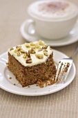 A piece of carrot cake with cappuccino