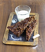 Pecan chocolate cake and a glass of milk on a slate