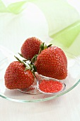 Three strawberries with red sugar