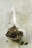 Dried tea leaves on metal spoon