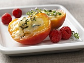 Baked peach with cheese stuffing and raspberries