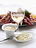 Aioli, a glass of white wine and seafood platter