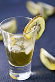 Herb liqueur with ice cubes and kiwi fruit