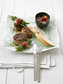 Grilled pork medallions with beans and plum sauce