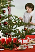 A Christmassy table, with a woman lighting a candle on the Christmas tree