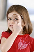Girl holding heart-shaped biscuit cutter in front of her eye