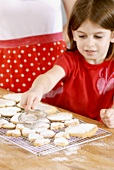 Girl dusting biscuits with icing sugar
