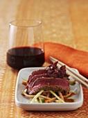Marinated beef fillet with sesame seeds on julienne vegetables