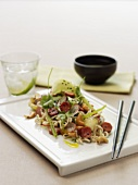 Asian noodle dish with sausage slices and radishes